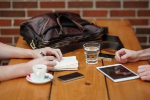 a table with coffee cup and water glass with hands on a note book and ipad